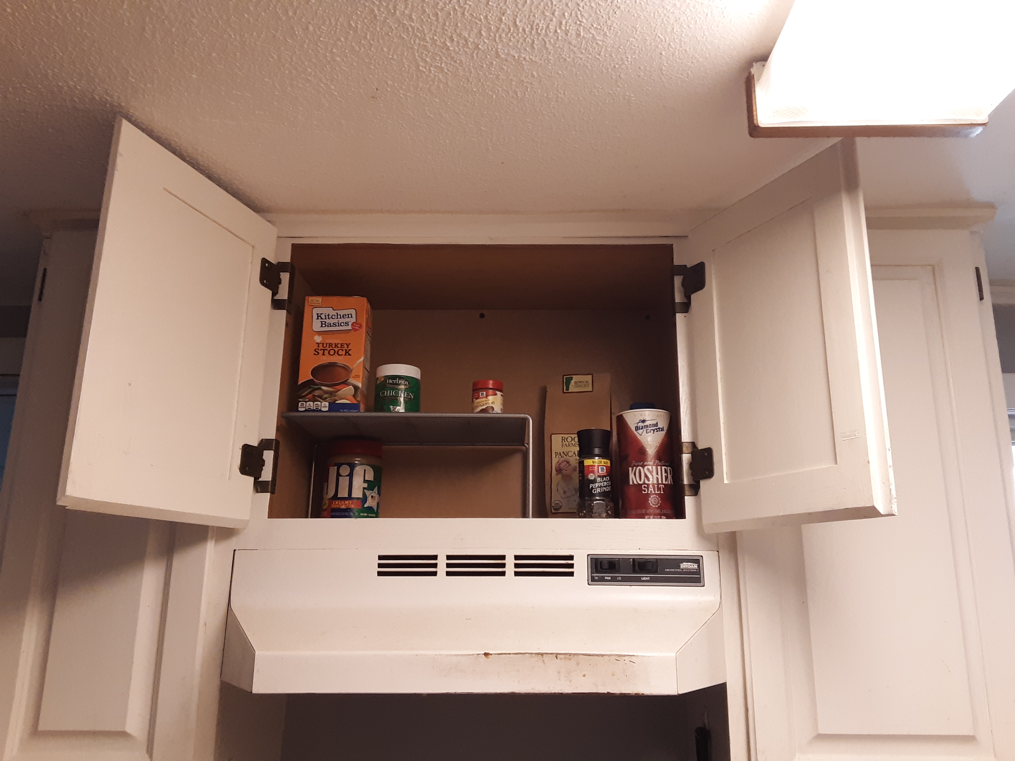 A cleared cupboard with room for more soups, spices, etc.!