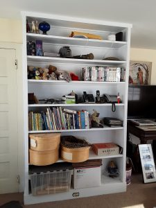 A bookcase before we cleared its cluttered shelves
