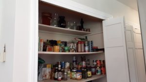 Top shelf vases wiped, and the second shelf better organized, including a small tower of tuna cans to the right