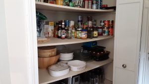 One shelf organized with condiments, the one below it with some bowls, casseroles and a dumplings maker