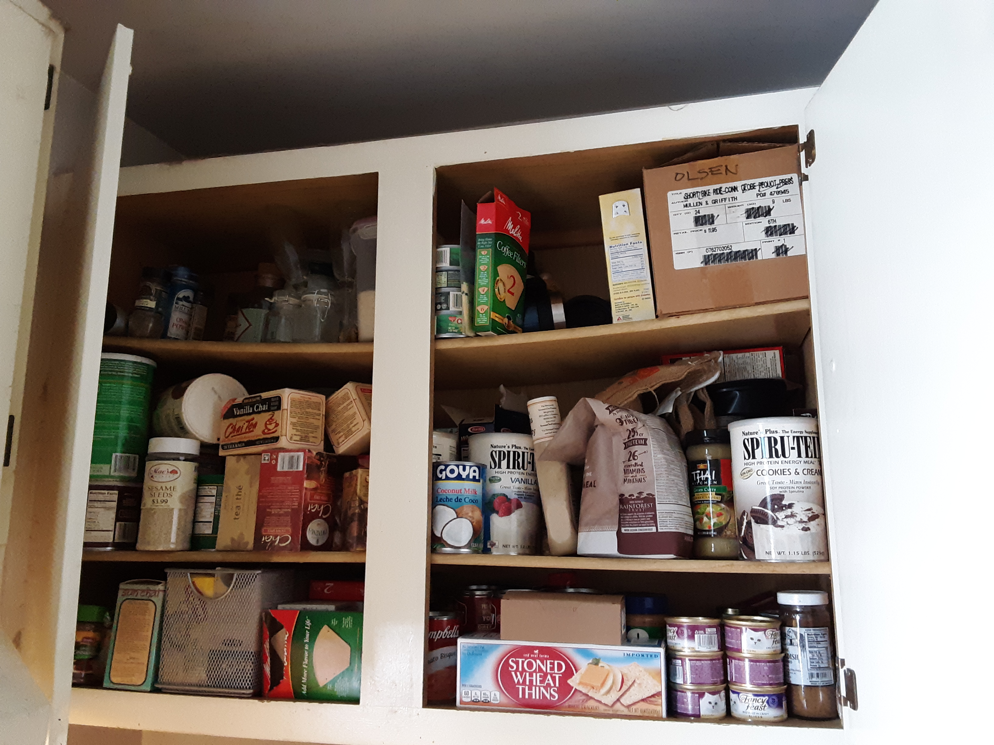 A very full kitchen cupboard before organizing it.
